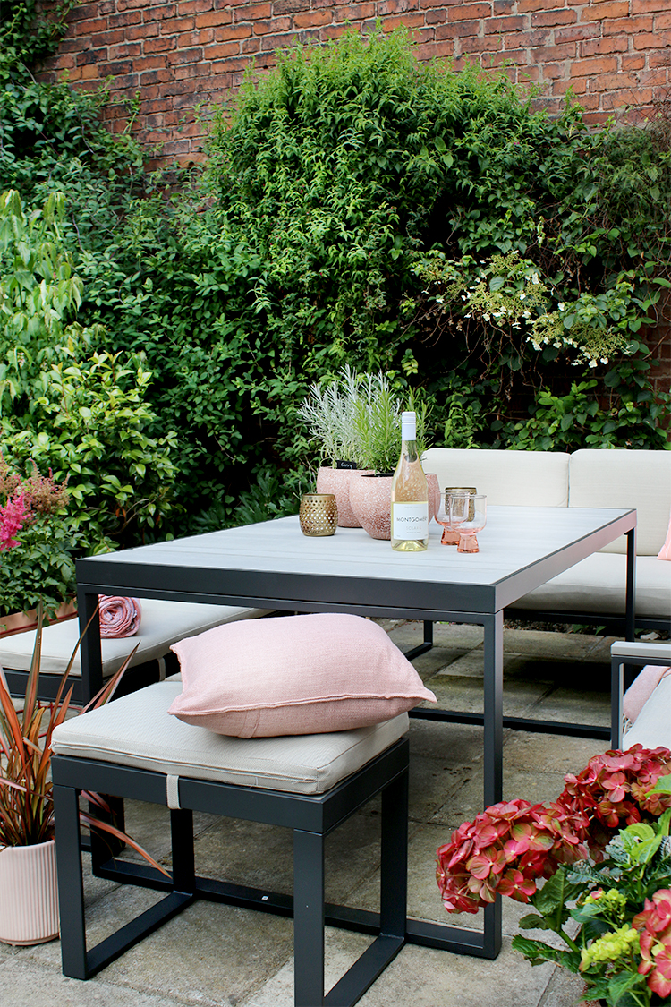 outdoor dining set styled with pink and green accents