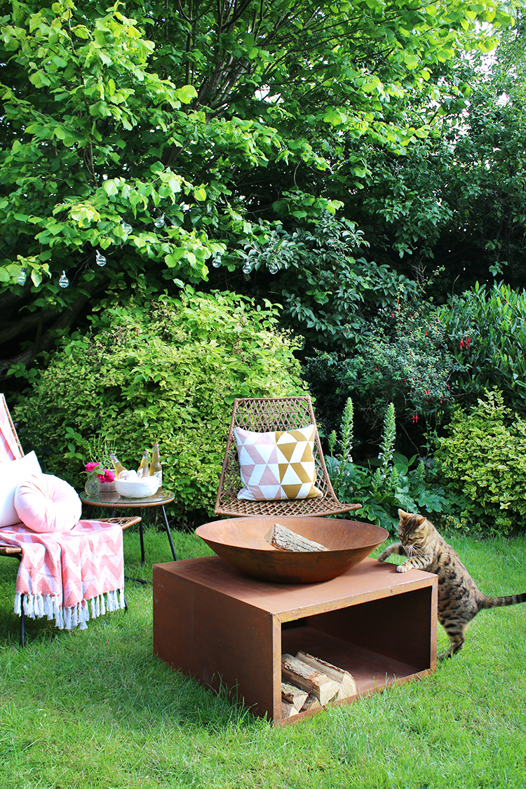 firepit at the back of the garden with wicker bistro chairs