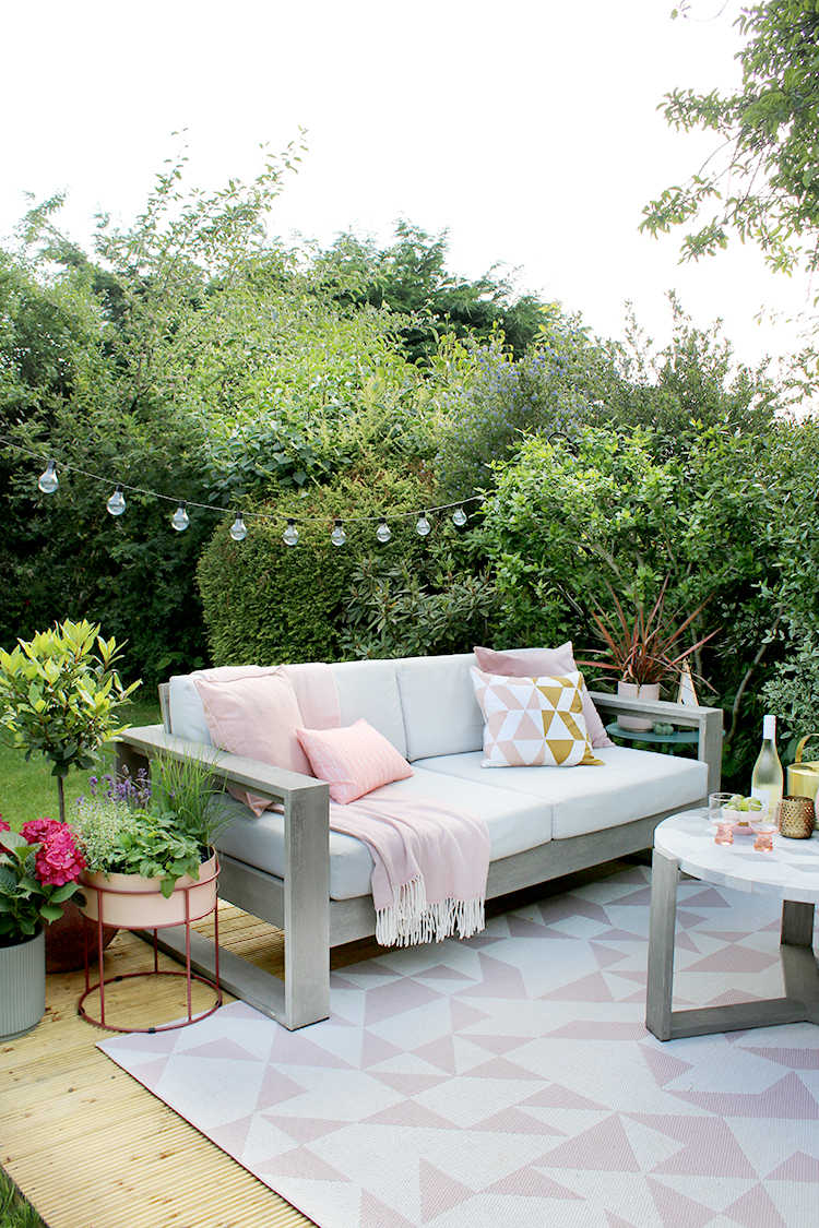 outdoor sofa with cushions, throws and outdoor rug in pinks and greens