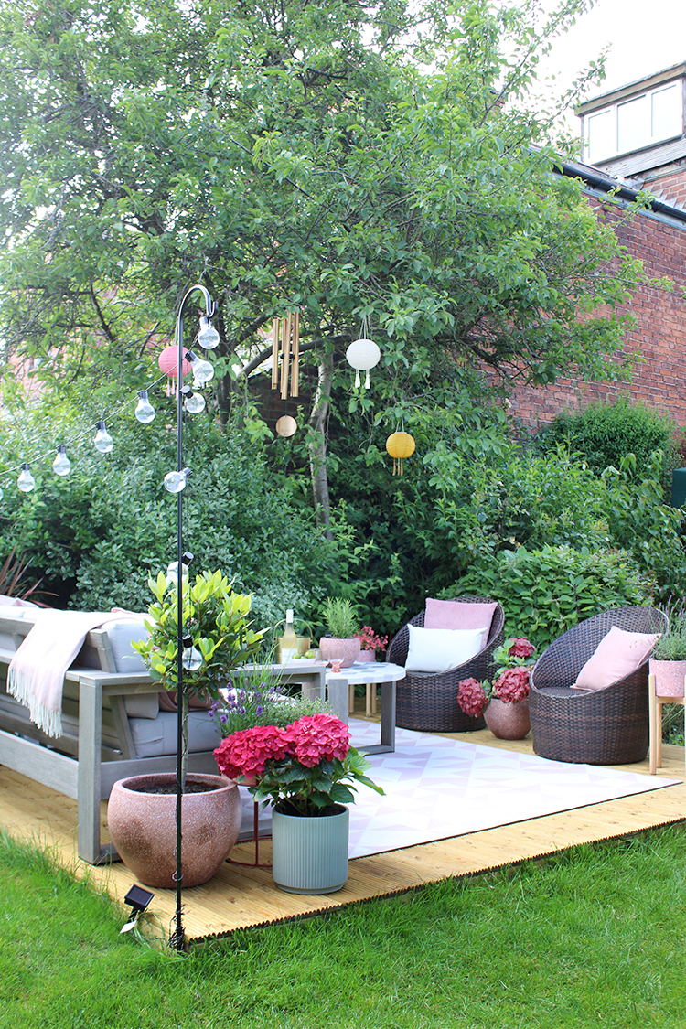 decked area in garden in pinks and greens with festoon lighting