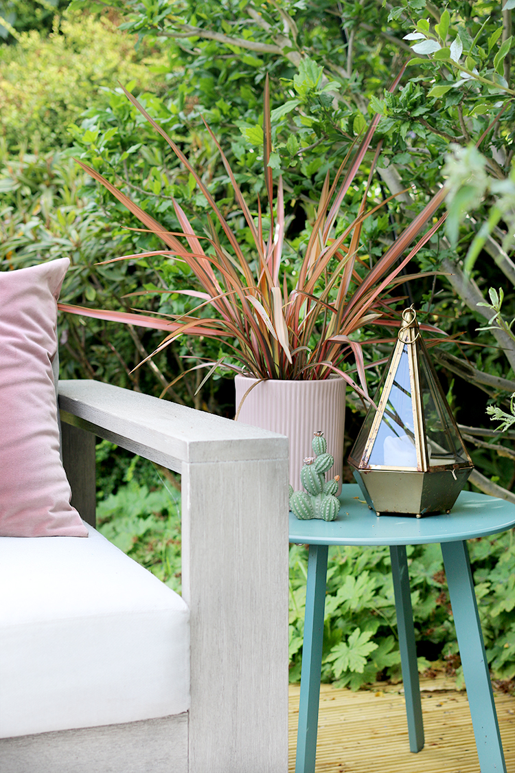 teal garden table with pink plants and gold hurricane