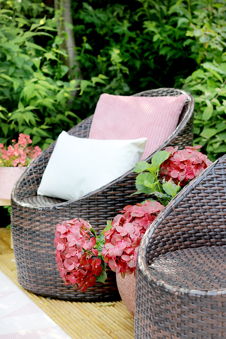 outdoor chair detail with pink cushions and hydrangea