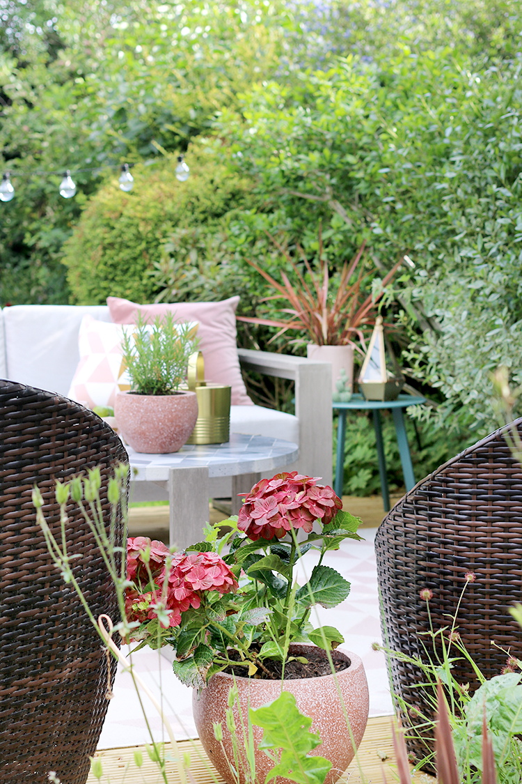 decking area in shades of pink and green styled with outdoor plant pots in pink