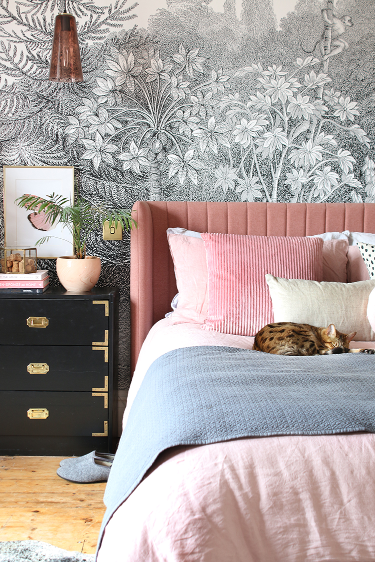 Pink bedroom with cat on bed and black and white wall mural