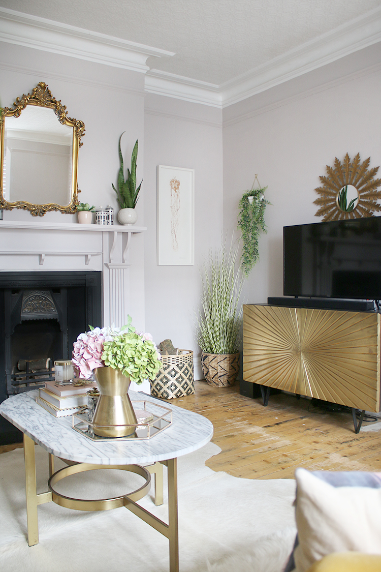 Gold TV stand with french style mirror above fireplace