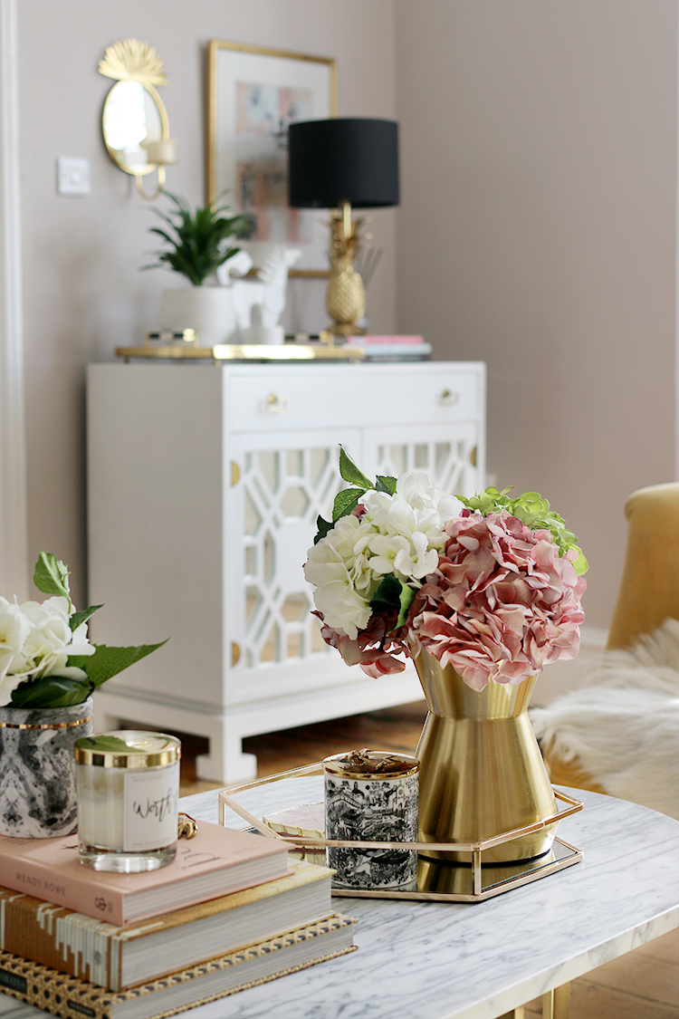 Coffee table styling with vintage cabinet in the background