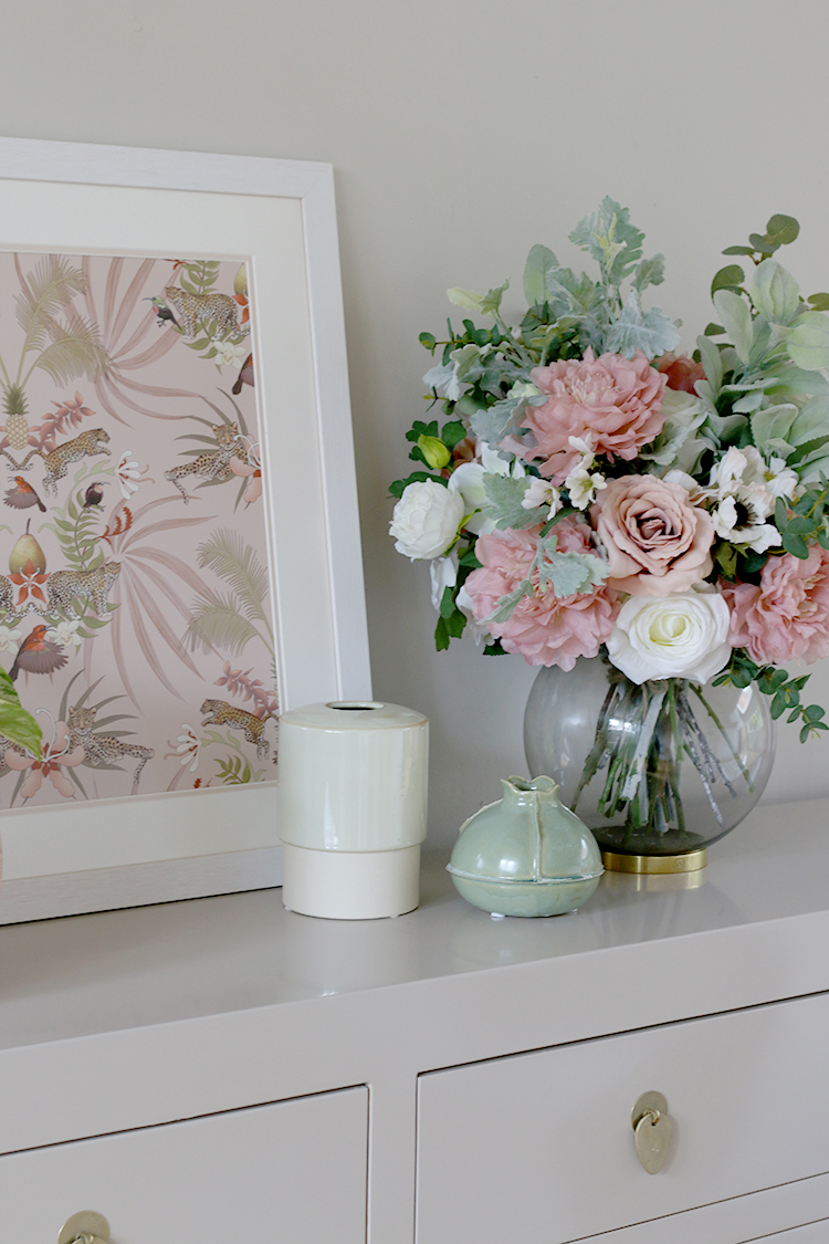 faux flowers and print vignette styled on sideboard