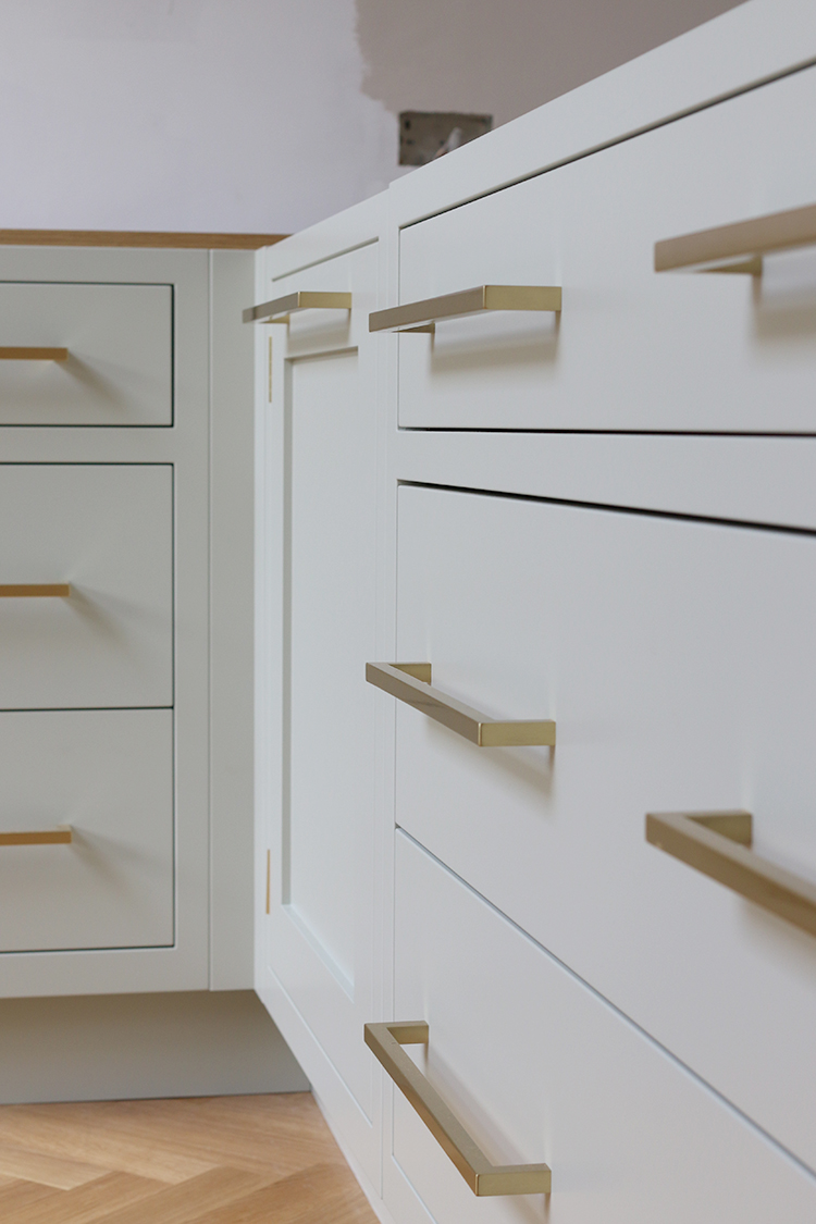 detail of kitchen drawers with brass hardware