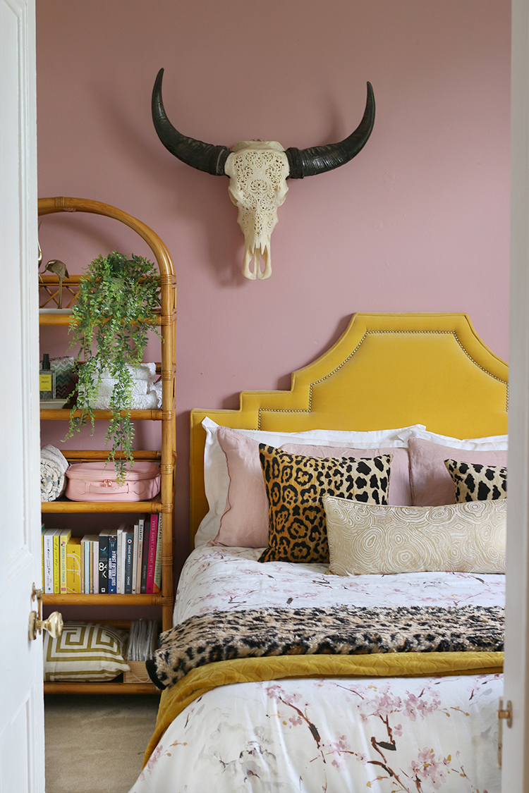 pink and gold guest bedroom with vintage rattan shelving unit and yellow velvet art deco headboard