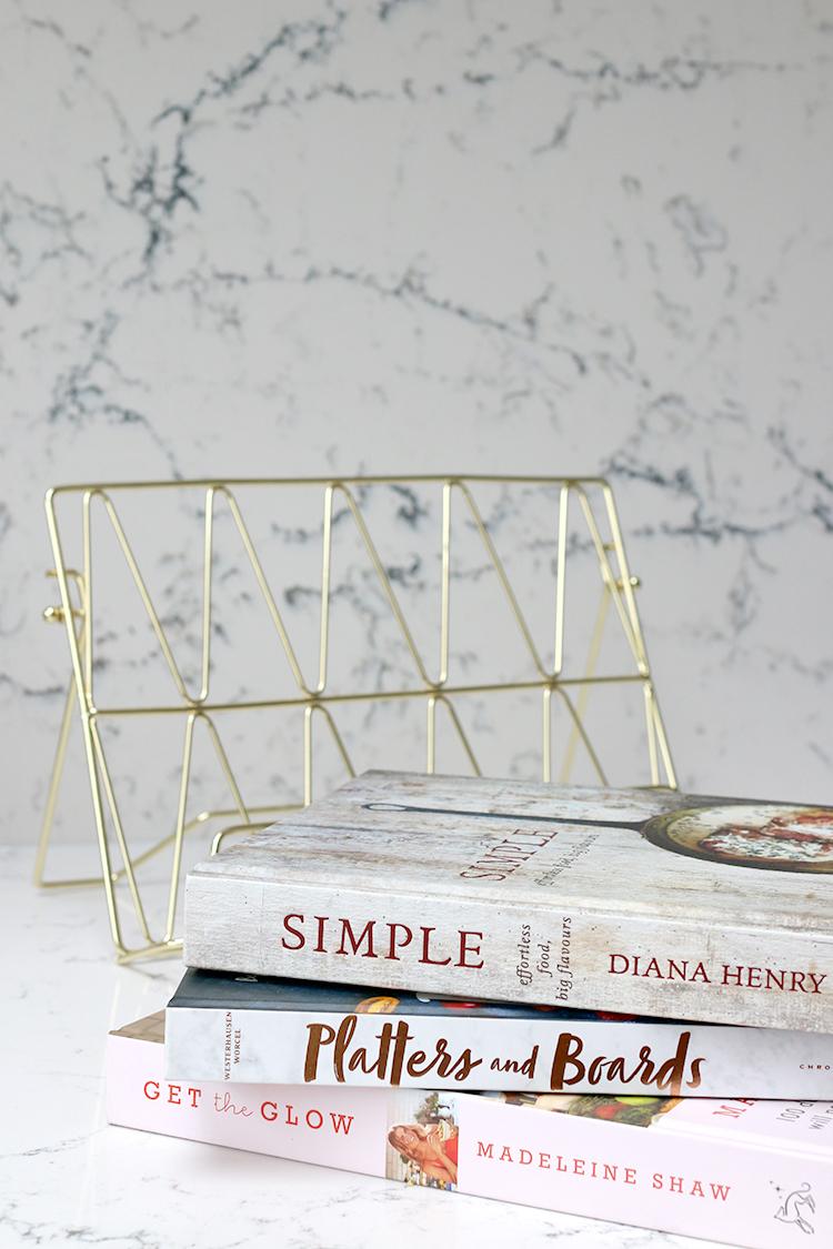 cookbooks and gold cookbook holder against quartz marble-effect worktops and backsplash