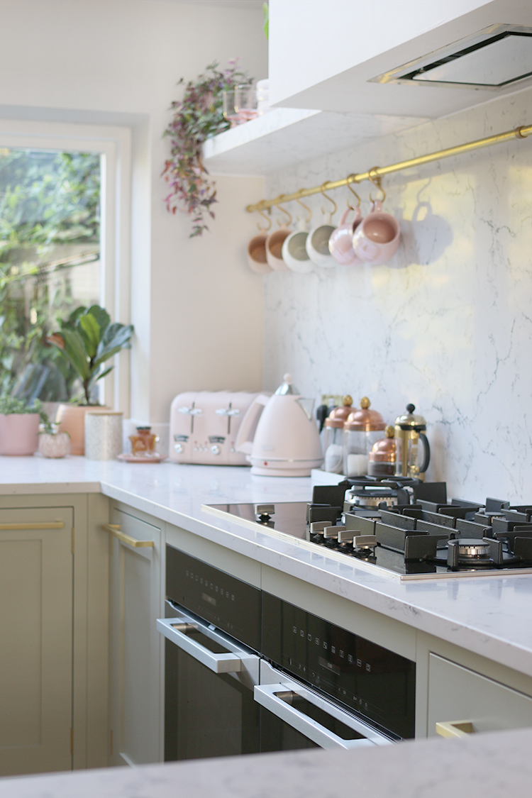kitchen in pale green with Caesarstone White Attica backsplash and worktops
