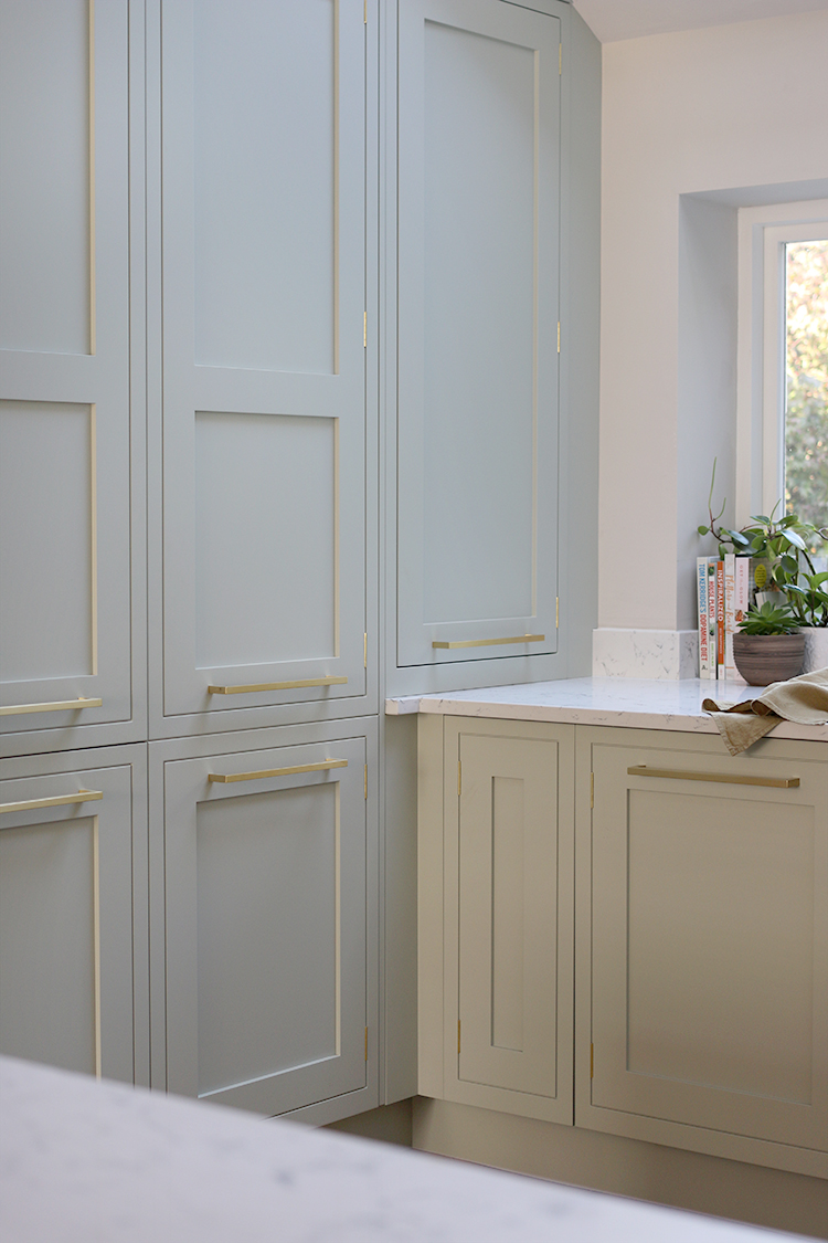 wall height kitchen units in pale green with gold hardware