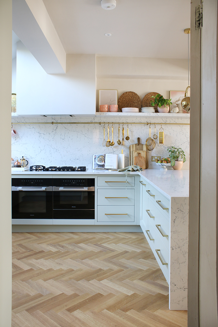 Pale green kitchen with parquet flooring and gold and pink accents