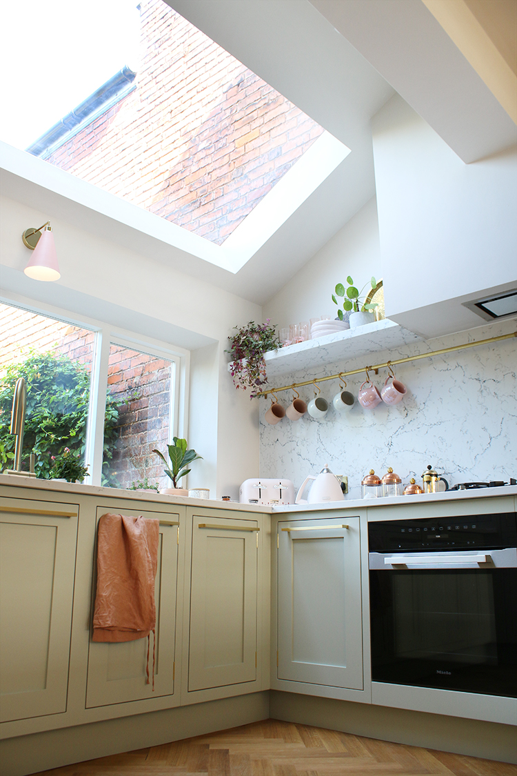 kitchen rooflight with pale green kitchen with gold and pink accents