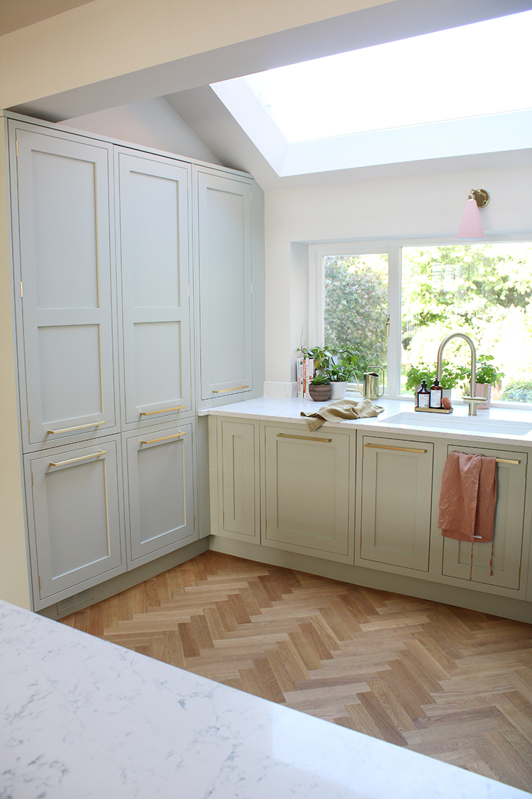 kitchen wall units in pale green with parquet flooring and rooflight