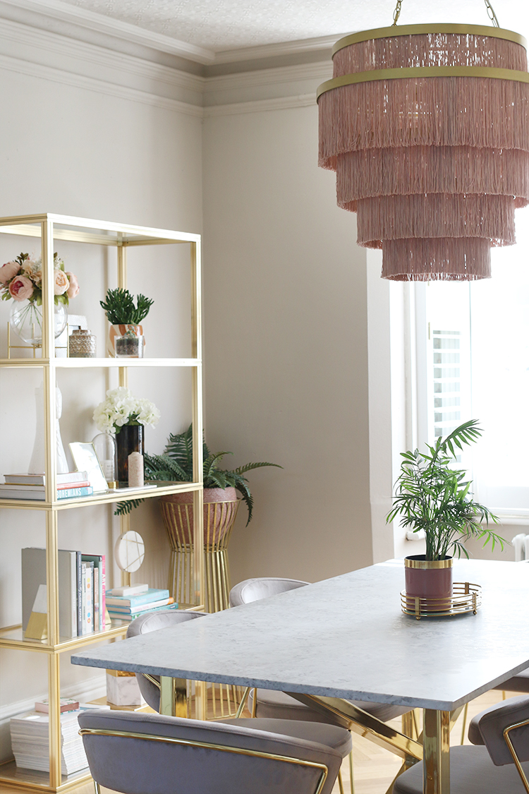dining room with fringe ceiling light and gold vintage shelving unit