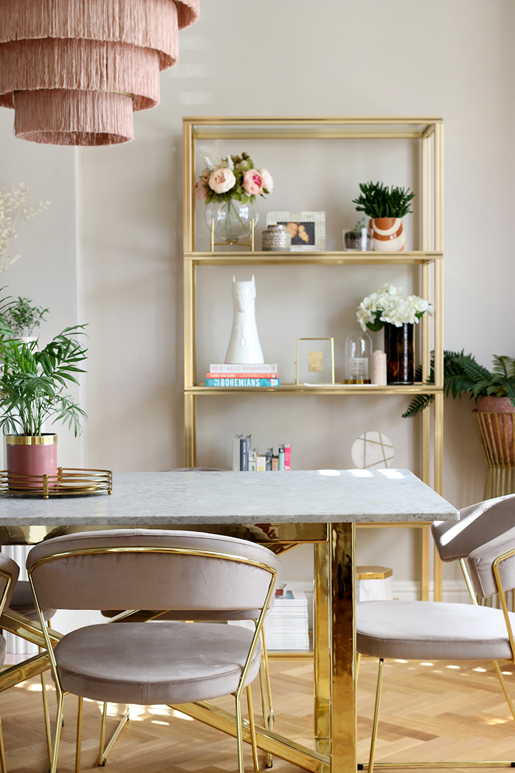 dining room with grey velvet chairs and gold and marble table with vintage brass shelving unit