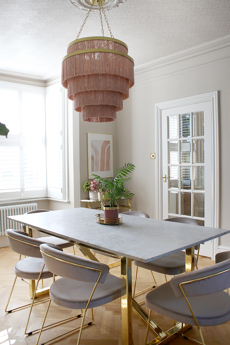 marble dining table with gold base and velvet chairs with pink light fixture