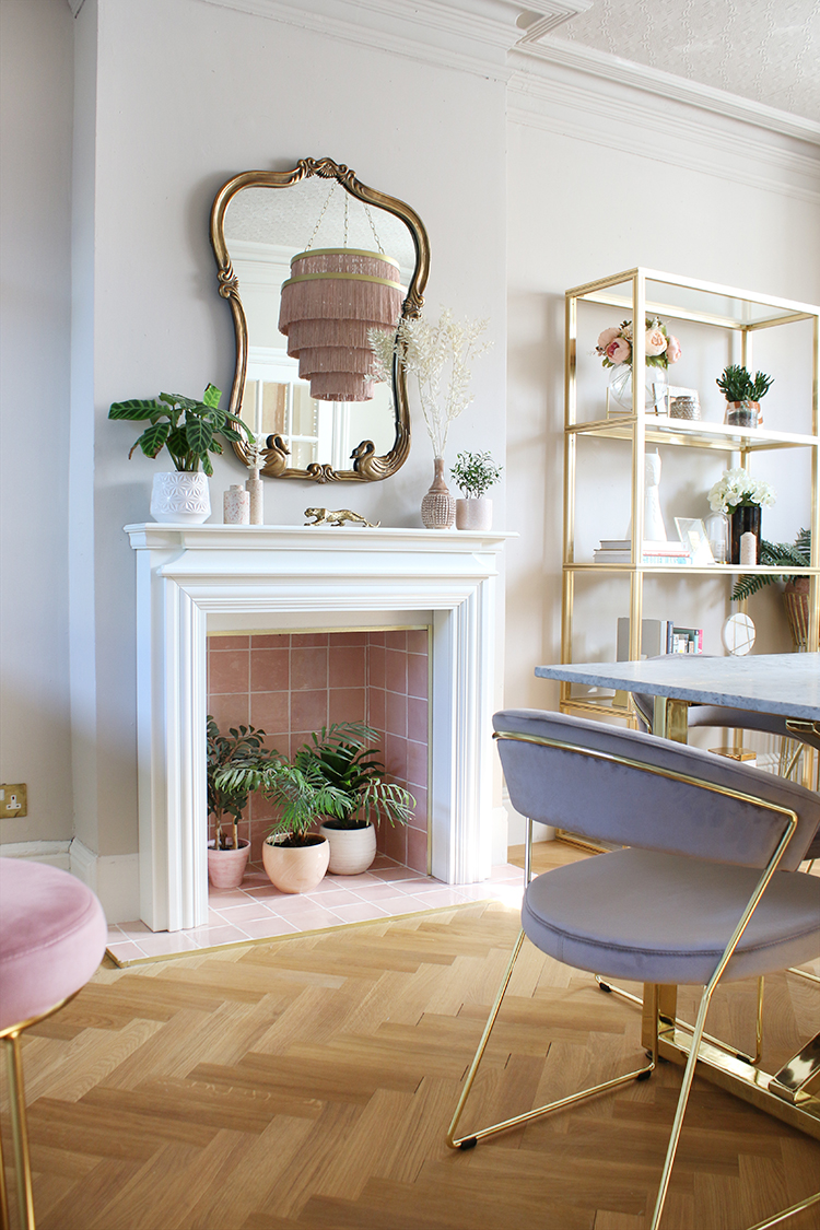 pink tile fireplace in dining room with ornate brass mirror