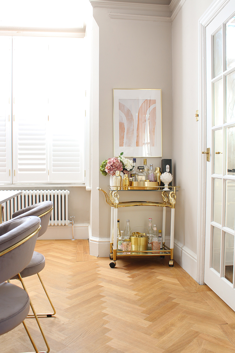 vintage bar cart with taupe walls and parquet flooring