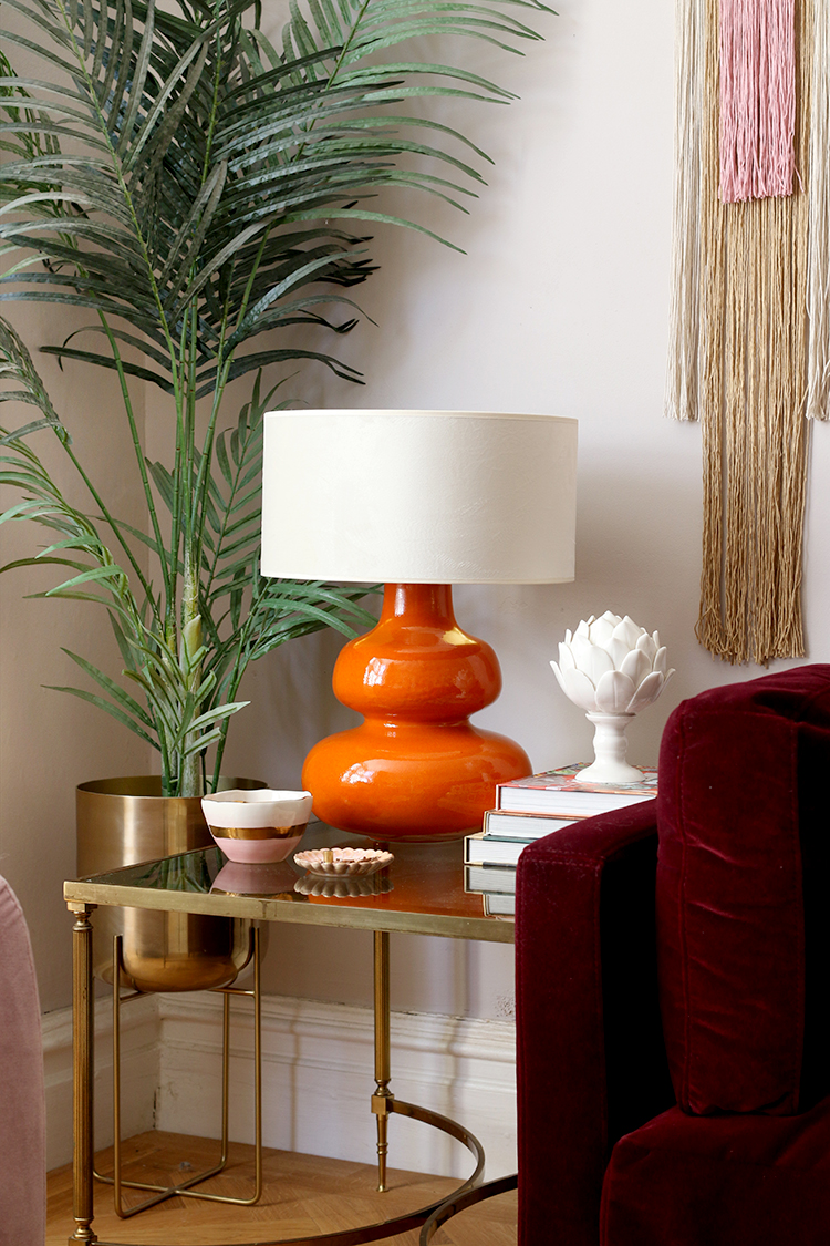 orange lamp with burgundy sofa and wall hanging