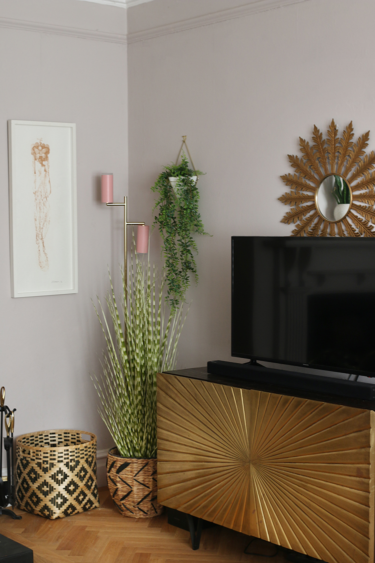 gold tv cabinet with plants
