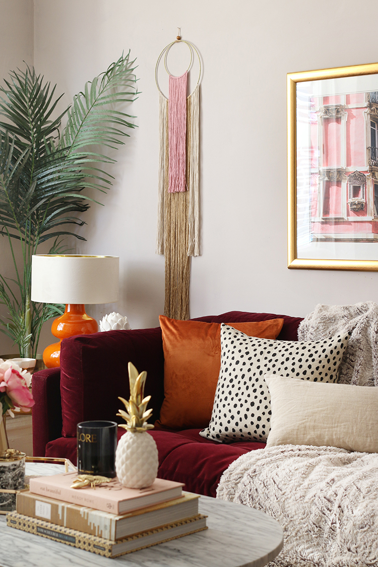 Living room in pink and orange tones with burgundy sofa