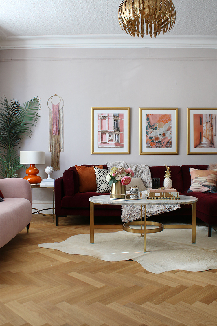 living room with parquet floors, burgundy and pink sofas and touches of rust orange