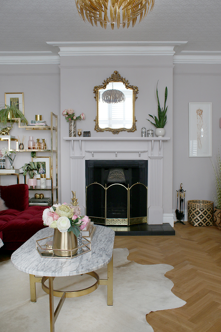 Victorian fireplace with parquet flooring and ornate french-style mirror