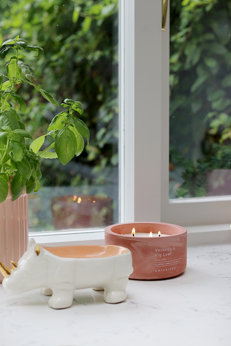 What to do before lighting your candle for the first time - pink 3-wick candle on kitchen worktop in front of window