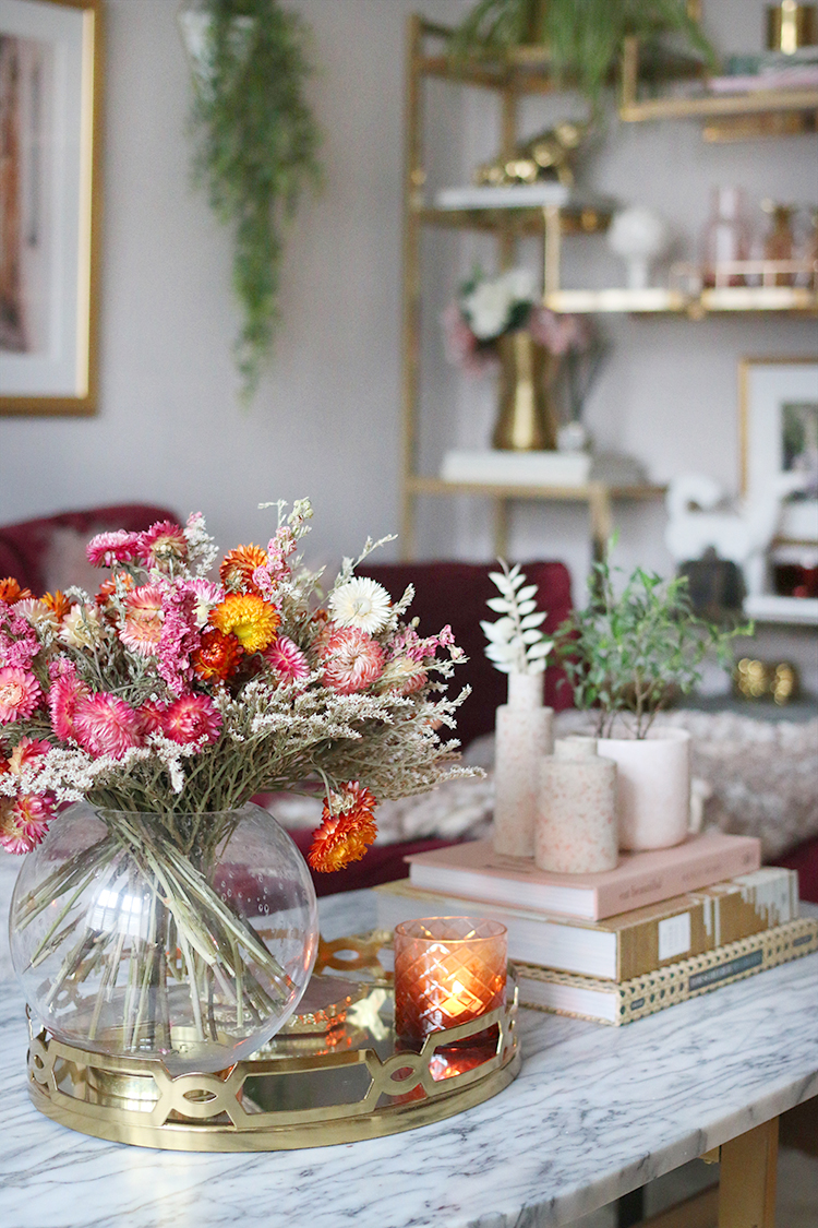 Living room with coffee table styled in pink orange burgundy with gold accents