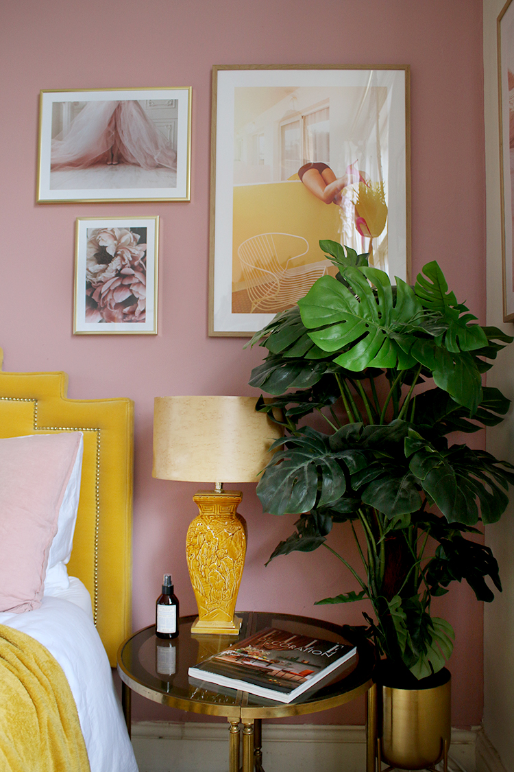 Gallery wall in bedroom in pink and yellow