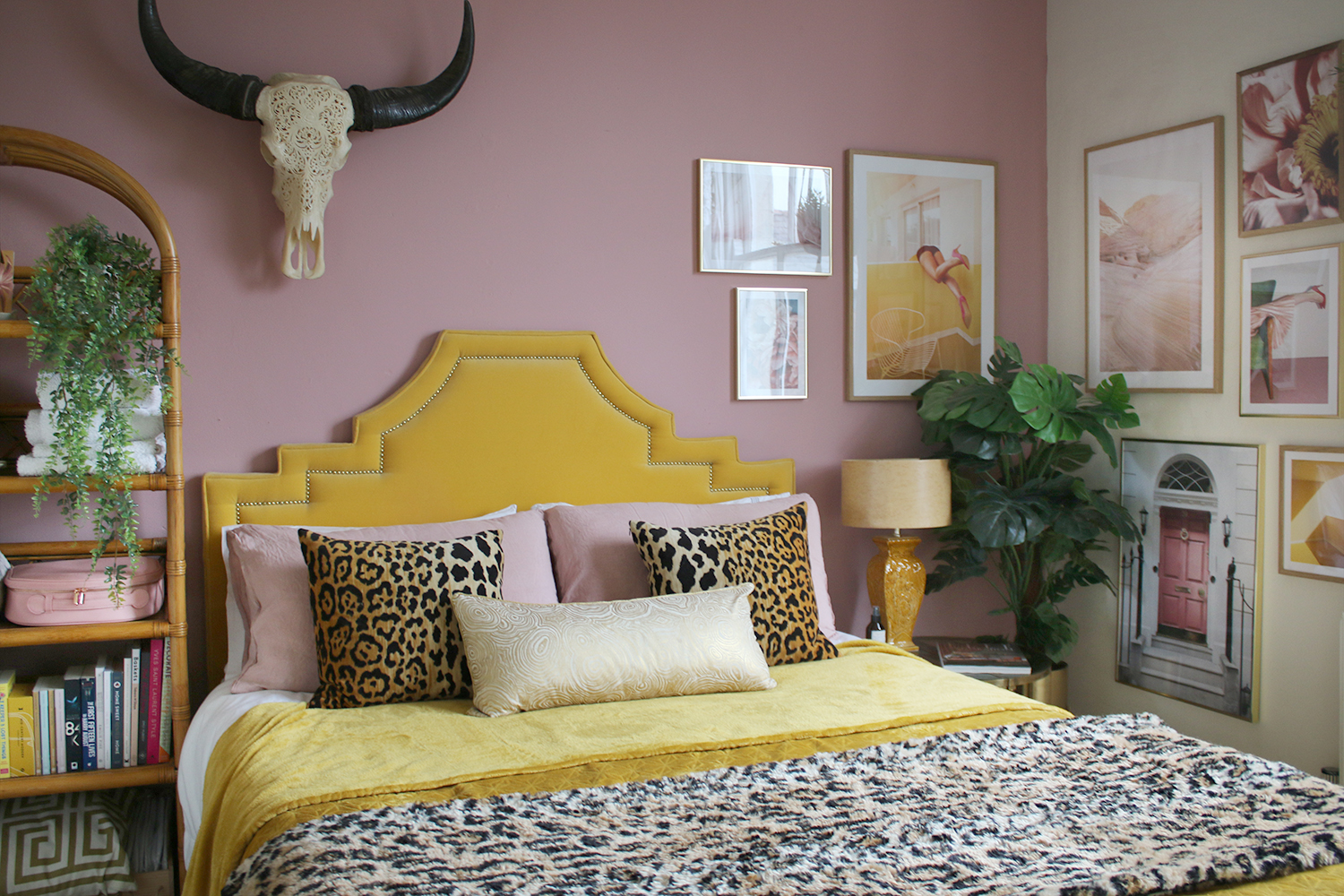 Pink and yellow bedroom with gallery wall and vintage rattan shelving unit