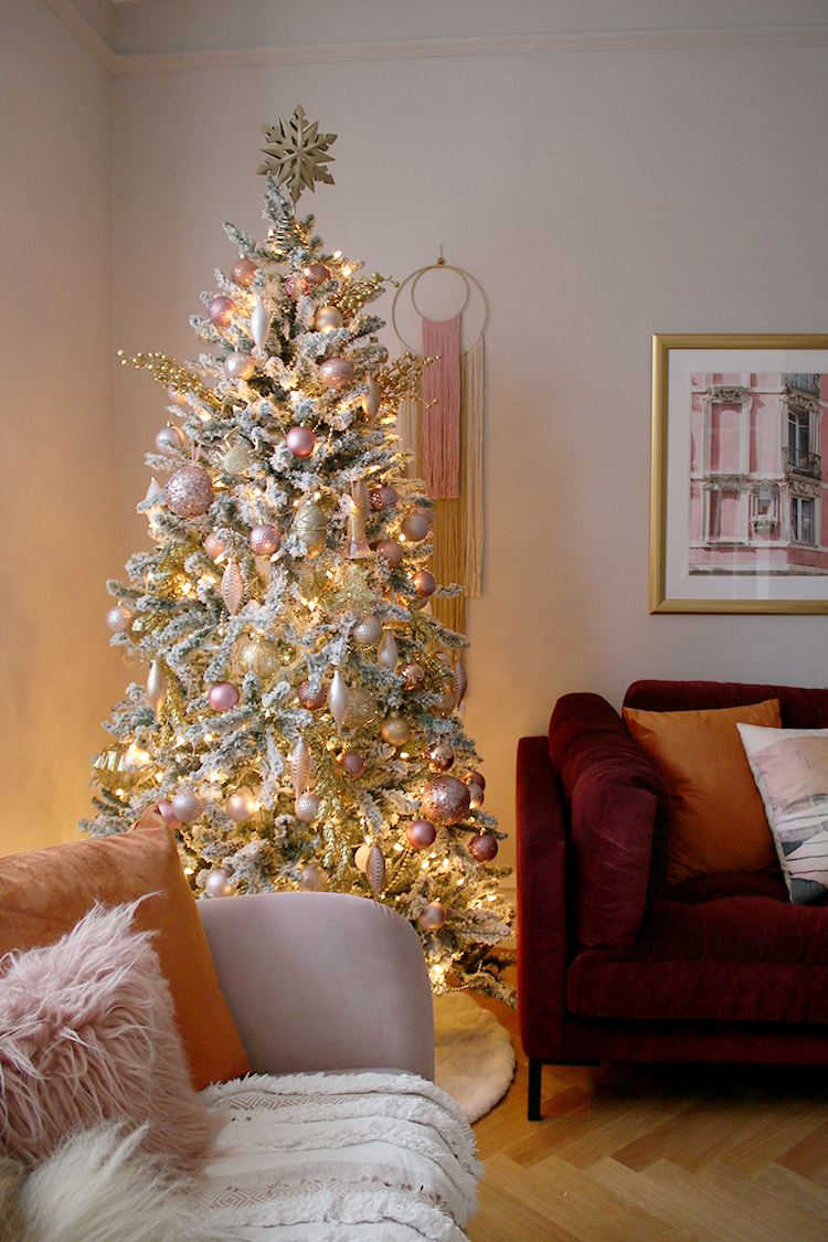 Pink flocked Christmas tree in corner with burgundy and pink sofas