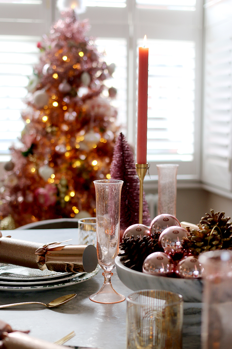 Christmas dining room table setting with pink tree in background