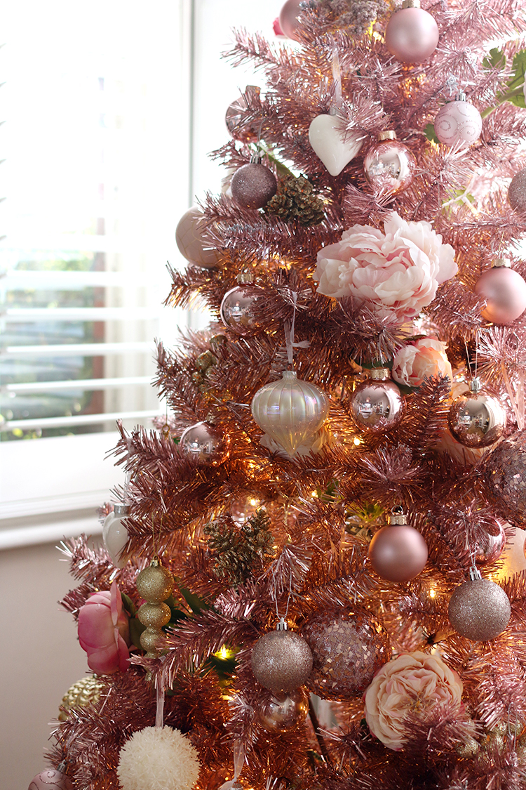 pink tree decorated with faux flowers for Christmas
