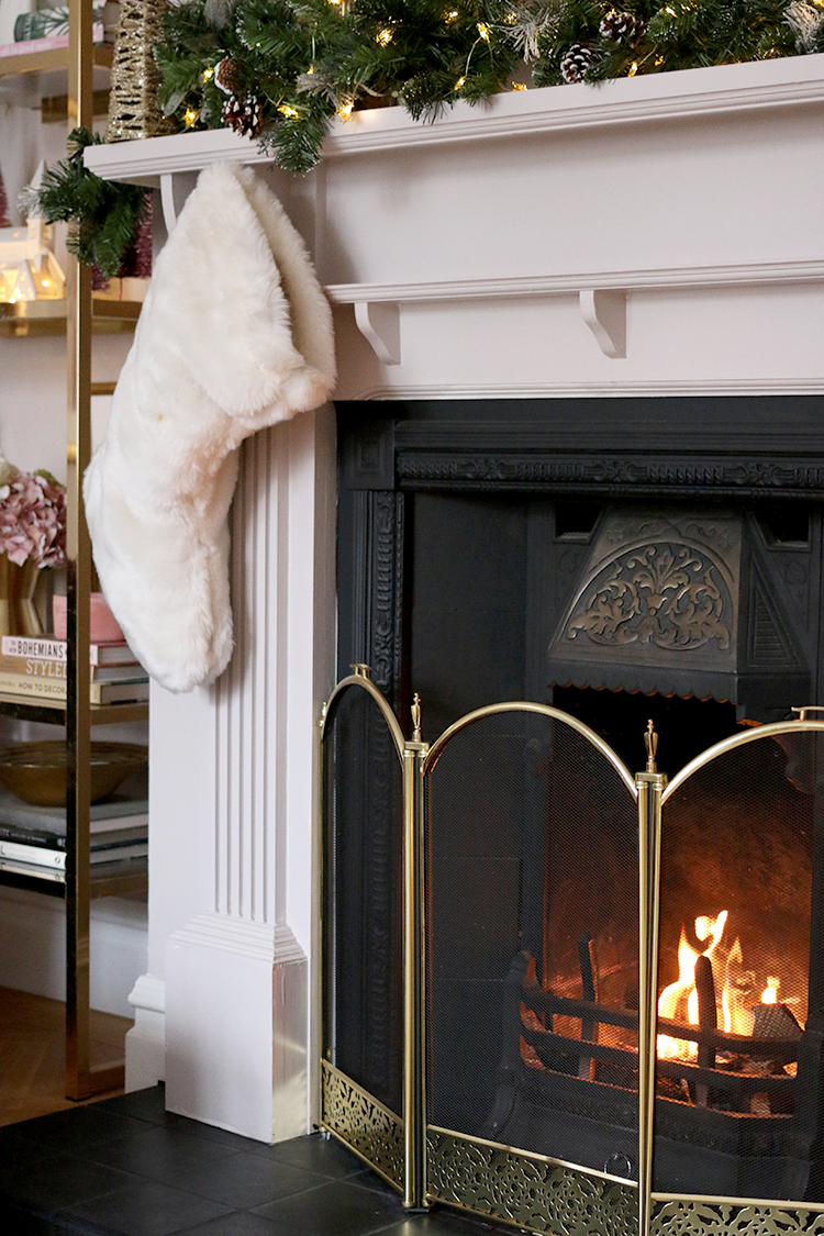 roaring fireplace with Christmas decorations on the mantle and white faux fur stocking