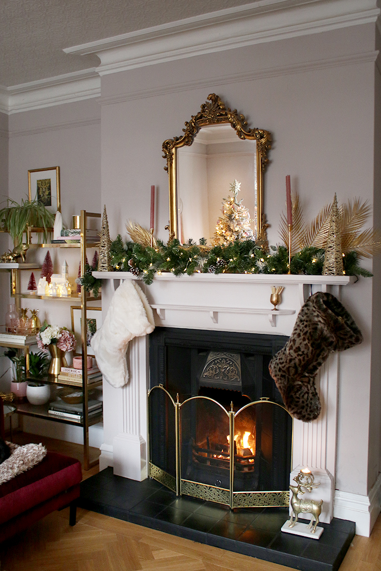 Victorian style fireplace decorated for Christmas with garland lights and stockings and ornate gold mirror