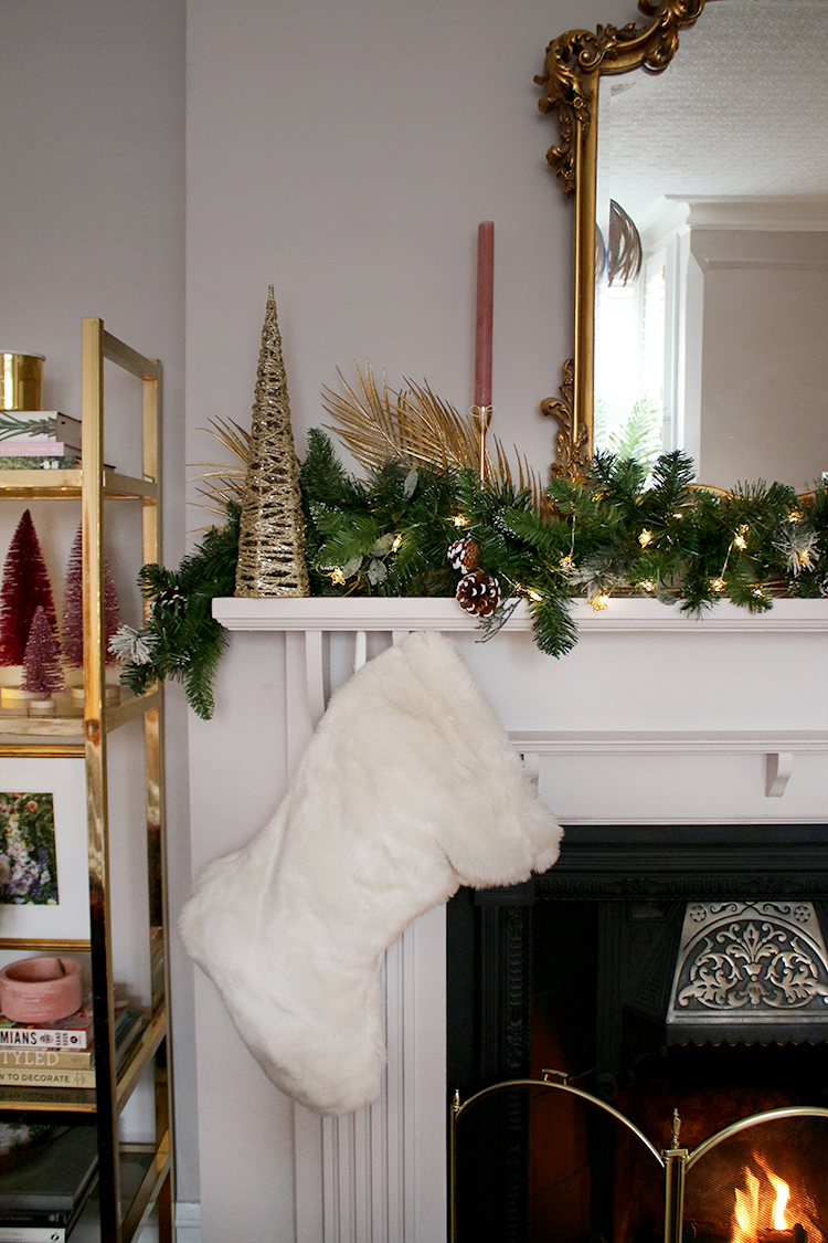 Fireplace mantle with faux white Christmas stocking and pink candles