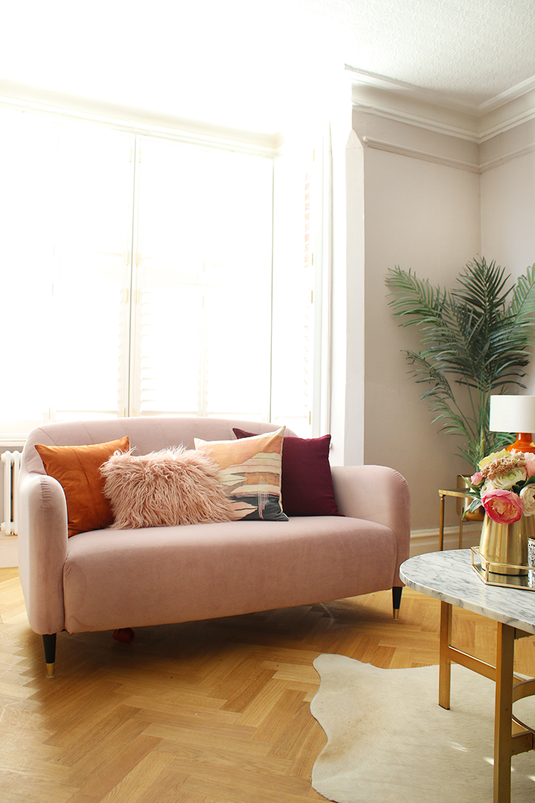 pink sofa in Victorian living room with parquet flooring and bay window