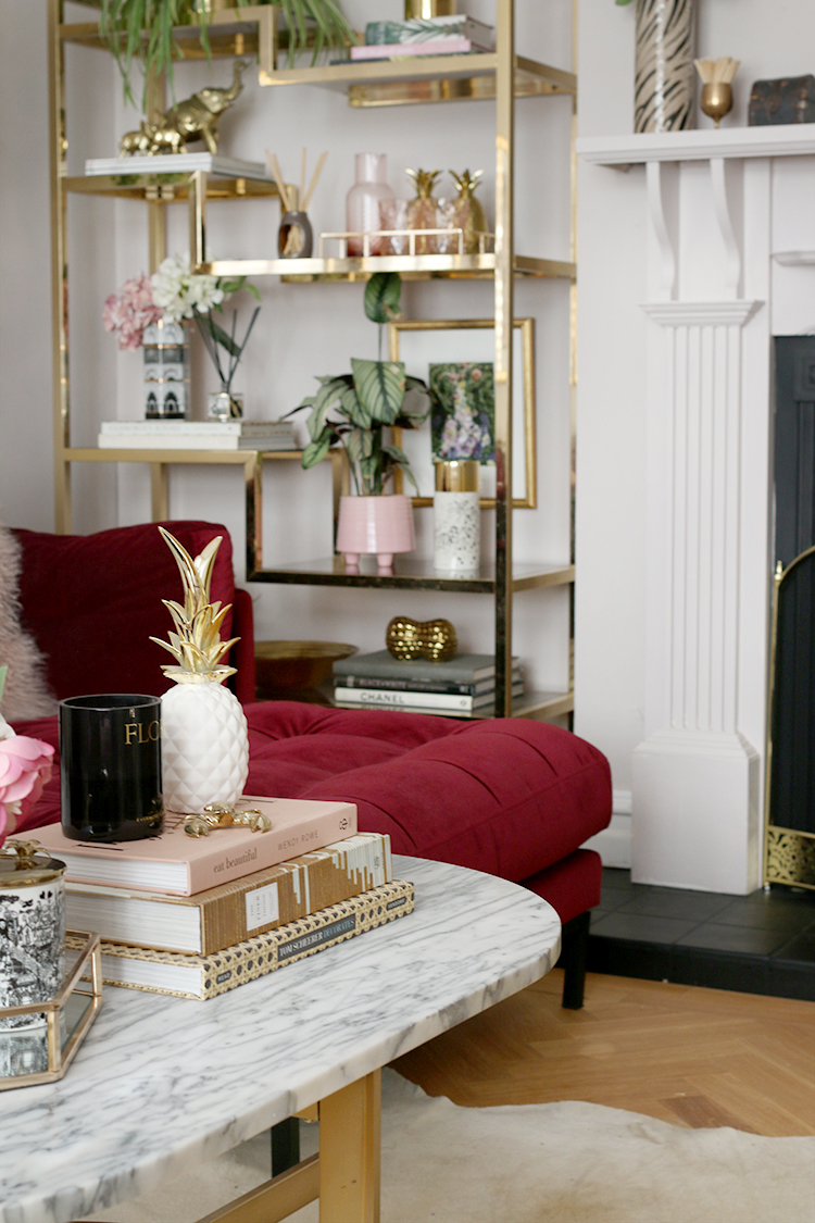 marble coffee table and vintage brass and glass shelving unit styled in pink and gold objects