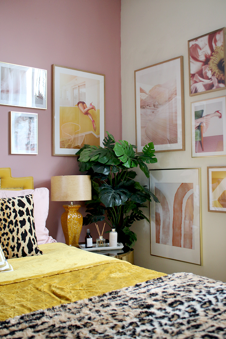 pink and yellow bedroom with corner gallery wall