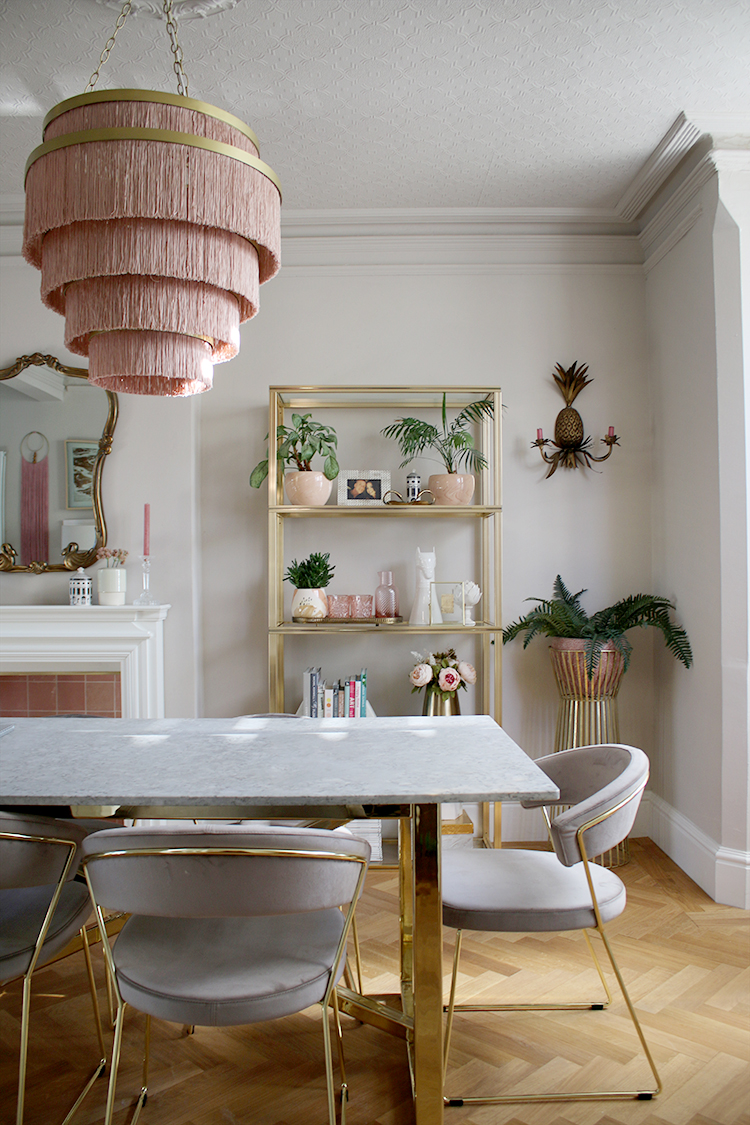 dining room with marble table and pink fringe light fixture