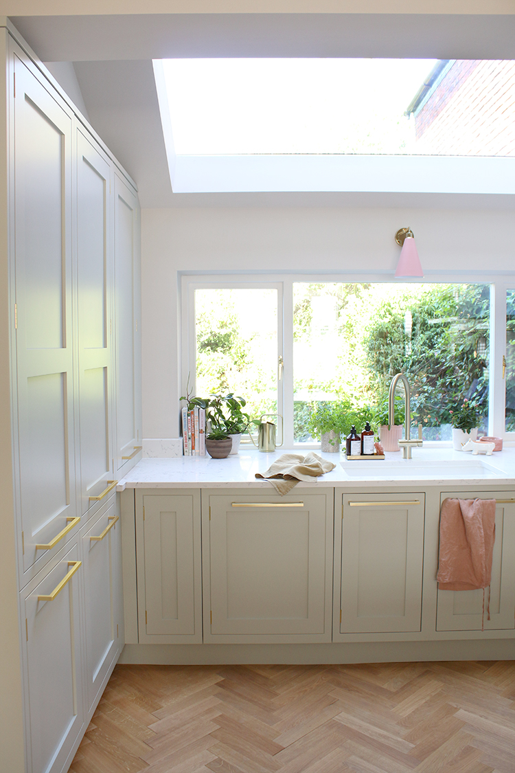 kitchen with large skylight in pale green and gold with parquet floors