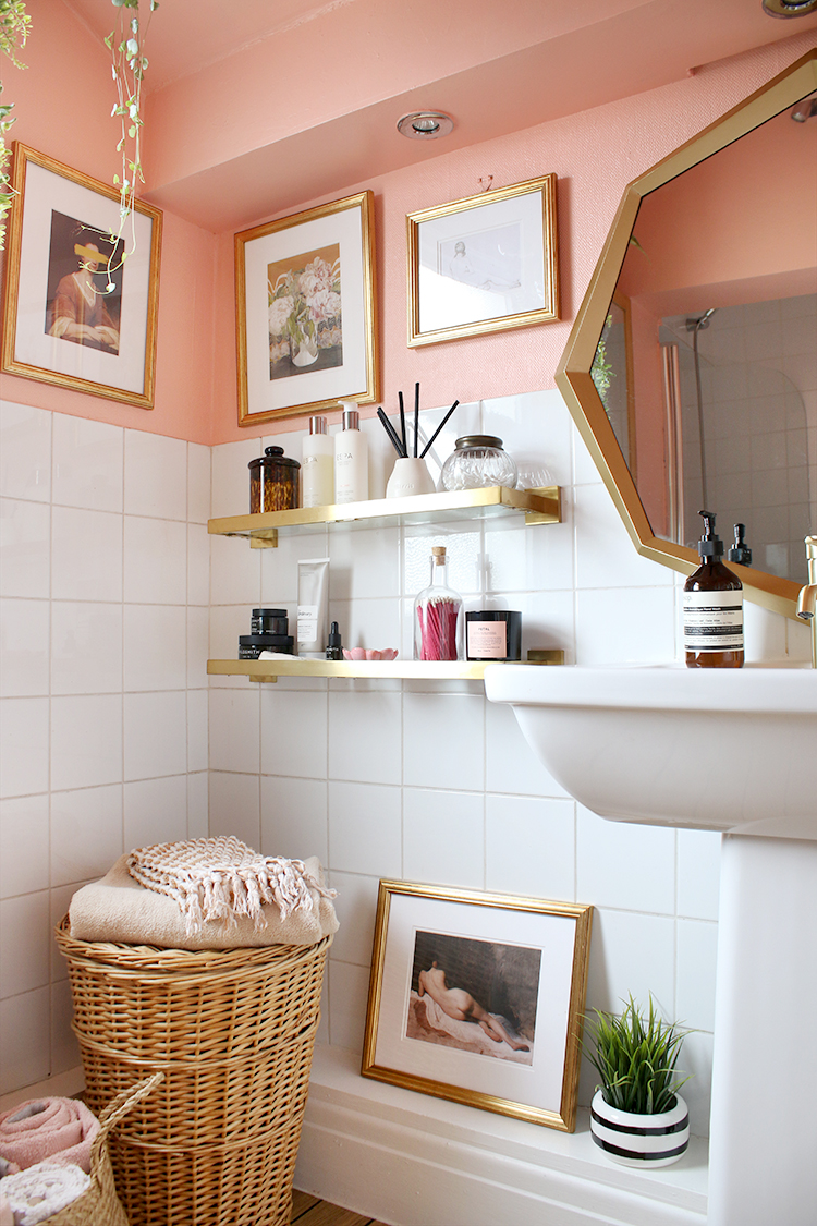 bathroom in peach white and gold with wicker accessories