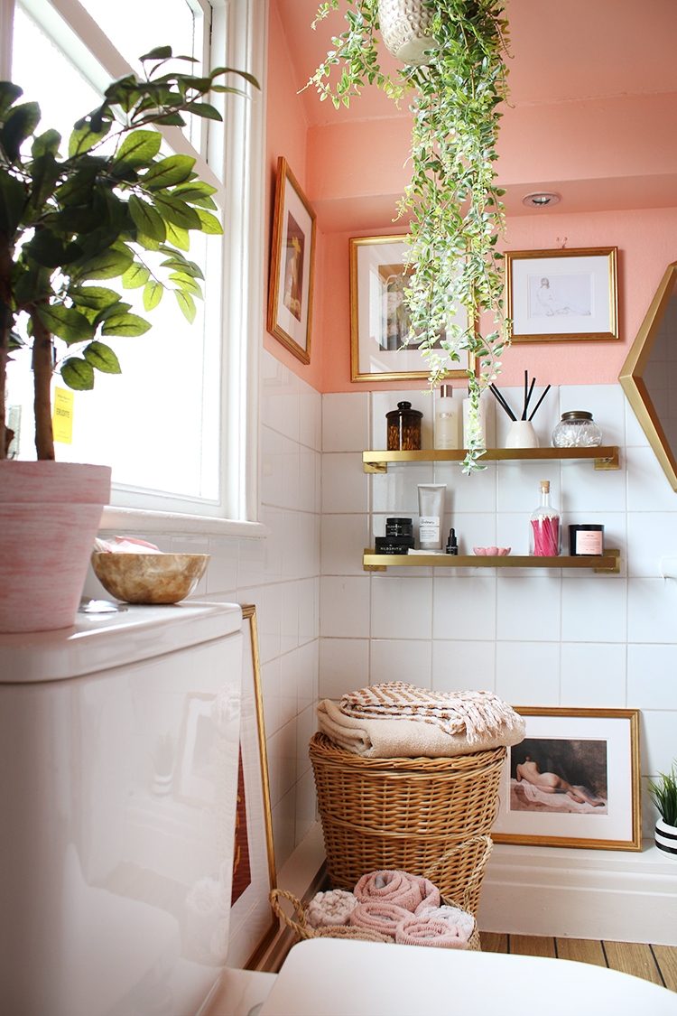 peach bathroom with greenery and gold accents