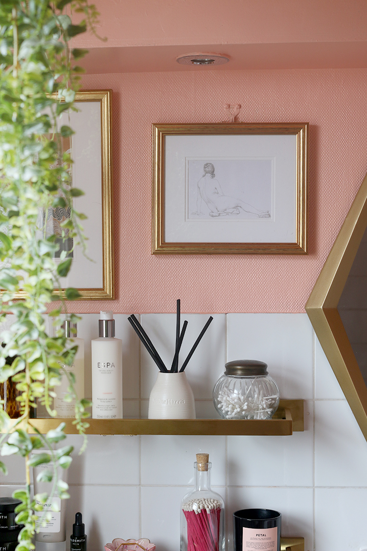 bathroom detail with peach paint vintage artwork and brass shelves
