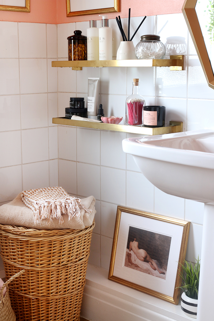 bathroom corner detail with white tiles and brass shelves