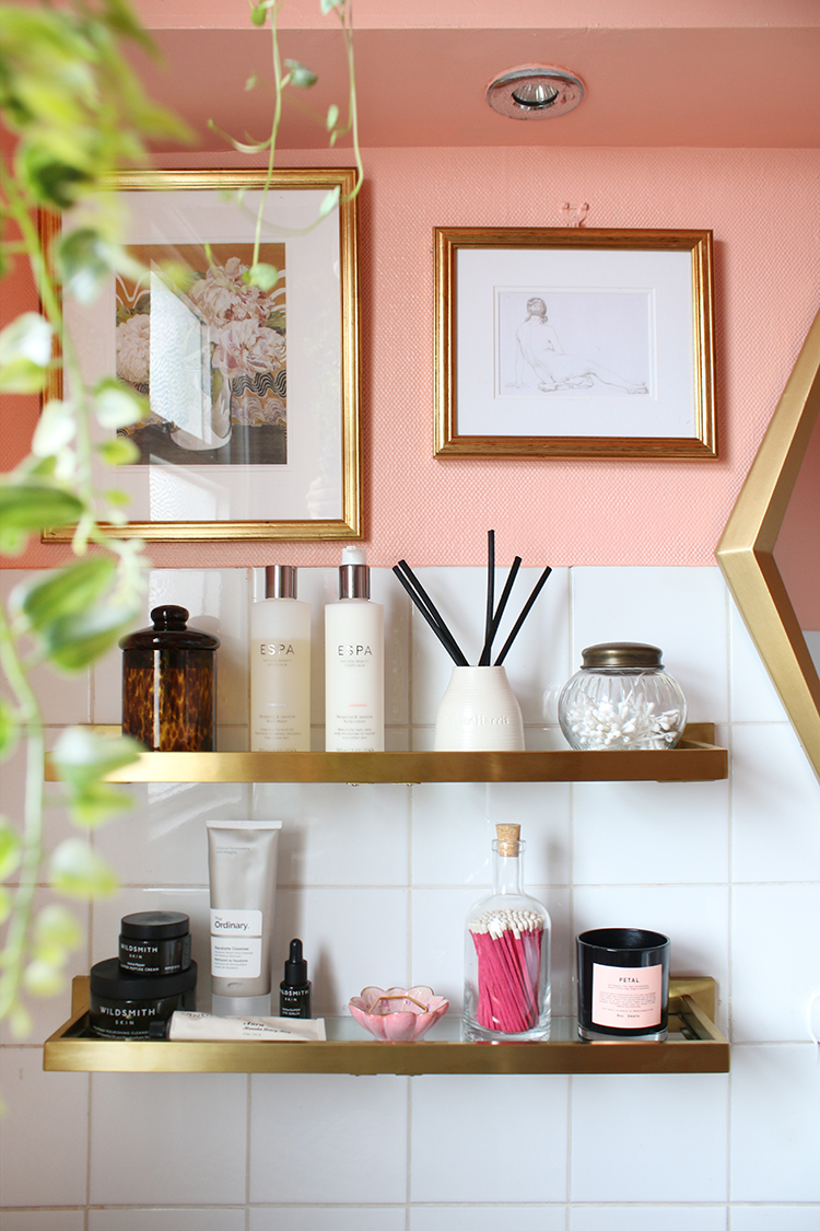 styled bathroom brass shelves with white tiles and peach paint