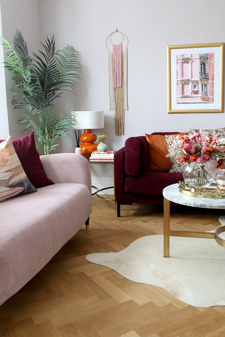 living room with pink and burgundy sofas with splash of orange